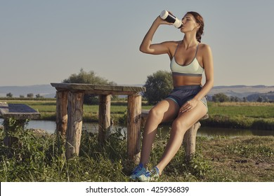 Attractive young lady in summer sportswear drinks water or energizing shake after the morning run while resting on a rustic wooden bench on the bank of a river.