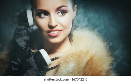 Attractive young lady with the vintage phone over the retro background