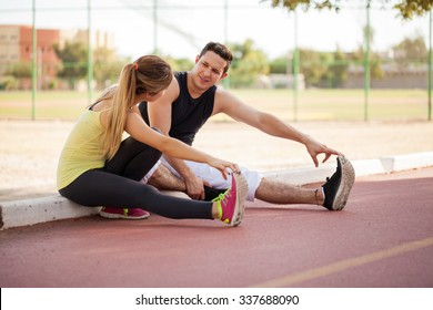 Attractive young Latin couple stretching their legs together before going for a run outdoors