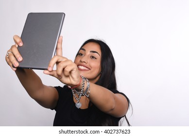 Attractive young latin woman taking selfie with tablet in a studio. Isolated white background.