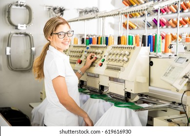 Attractive young Latin woman working with an embroidery machine in a factory and smiling
