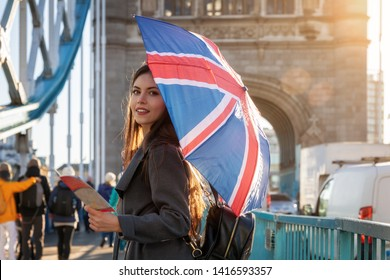 Attractive, young London traveler tourist with a British flag umbrella on the Tower Bridge in London, UK
