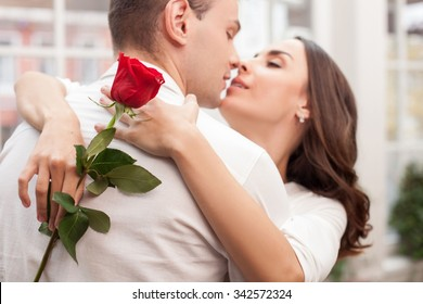 Attractive young loving couple is celebrating their anniversary. They are kissing with love. The man and woman are standing and embracing. The lady is holding a red rose