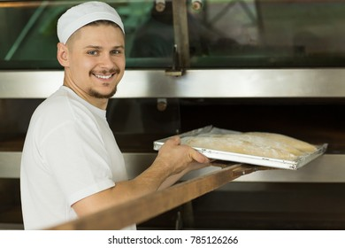 Attractive young male baker smiling to the camera over his shoulder putting dough on a tray into the oven baking bread at the kitchen of his bakery copyspace small business owner sales retail food job