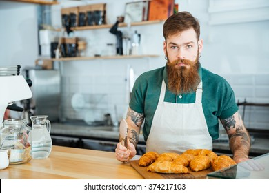 Attractive young male barista with bearrd and tattoo standing in coffee shop with croissants