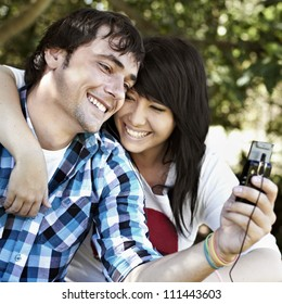 Attractive young male with beautiful young female having fun while smiling and listening to music