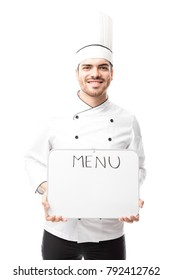 Attractive young male chef holding a board with the menu of the day and smiling in a studio