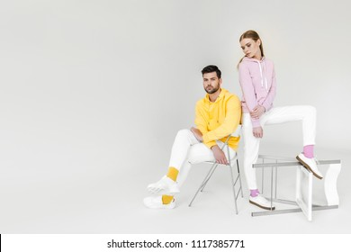 attractive young male and female models in colorful hoodies on white