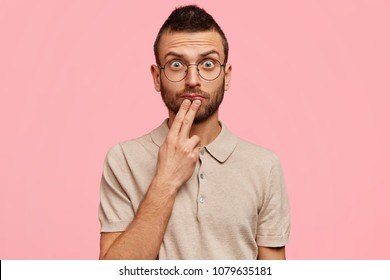 Attractive young male model with amazed shocked expression, looks with widely opened eyes att camera, has stubble, wears casual t shirt, isolated over pink background. Caucasian unshaven man