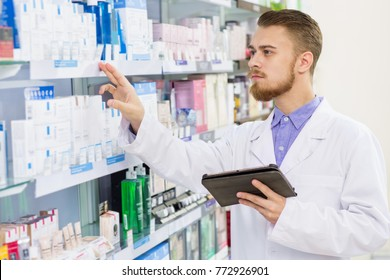 Attractive young male pharmacist checking stock in an aisle working at the drugstore using digital tablet technology profession occupation medical clinician healthcare service retail salesperson