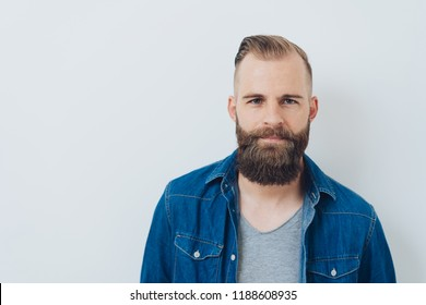 Attractive young man with a beard posing in front of a white studio background looking at the camera