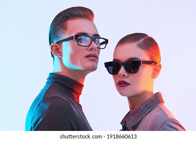 Attractive young man and beautiful young woman  are posing together in stylish glasses. Optics style. Fashion studio shot.