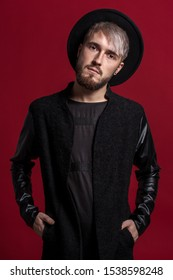 Attractive young man in black clothes with a hat on his head and with a beard and mustache on his face. Red background.