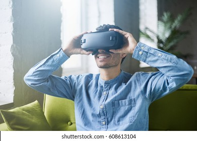 Attractive young man in blue denim shirt wearing virtual reality headset or 3d glasses sitting on green sofa at home. Handsome caucasian male using VR headset, playing video games. It is so real!