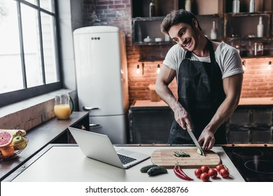 Attractive young man is cooking on kitchen with laptop on table while talking on smart phone.