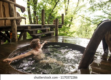 attractive young man with curly, fair hair is relaxing in the cold ooden tub after bathhouse. side view photo. relaxation concept