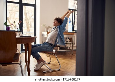 Attractive young man doing easy exercise at workplace at home stock photo