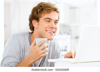 Attractive young man drinking coffee holding mug at home indoors