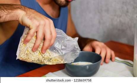 Attractive Young Man Eating Breakfast, Having some Cereal with Milk at Home in the Kitchen