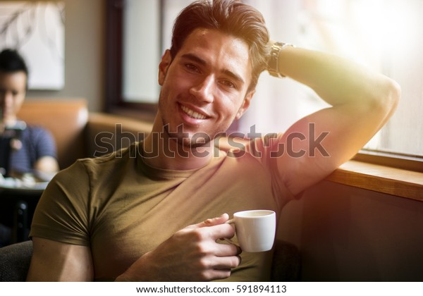 Attractive Young Man Eating Breakfast, Drinking Coffee and Smiling to the Camera