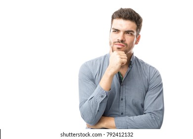 Attractive young man feeling thoughtful and looking towards copy space on a white background