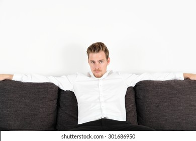 Attractive young man in his 20s sitting down in a sofa, wearing a white shirt and black jeans. Feeling relaxed leaning back.
