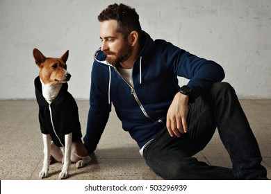 An attractive young man and his bassenji dog wearing matching hoodies sit on the floor next to white wall
