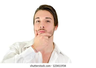 Attractive young man holding his chin, looking at camera and thinking