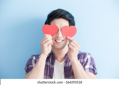 Attractive young man holding red love hearts over eyes isolated on blue background