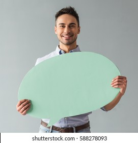 Attractive young man is holding a speech bubble, looking at it and smiling, on gray background