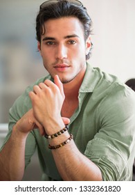 Attractive young man indoors wearing a shirt and beaded bracelets