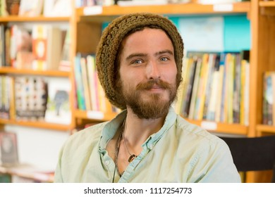 Attractive young man with knit cap in book store or library