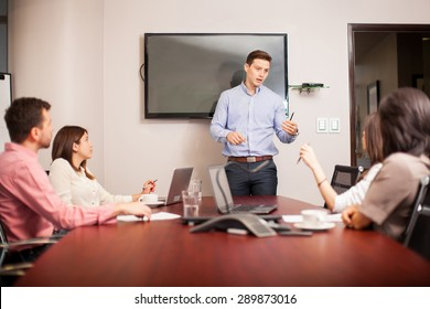 Attractive young man leading a meeting with his colleagues in a conference room