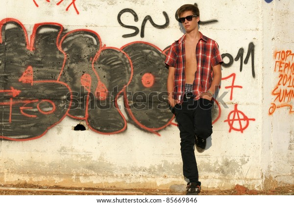 Attractive young man to leaning against the wall at a grafftiy wall.