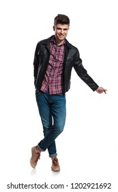 attractive young man in leather jacket snapping fingers while standing cross-legged on white background