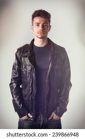Attractive young man with leather jacket and hands in jeans pockets, looking at camera