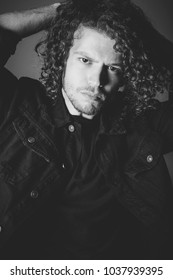 Attractive young man with long ginger curly hair studio portrait