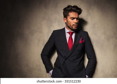 Attractive young man looking down while holding his hands in pockets.