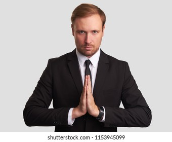 attractive young man meditating. Serious business person looking at camera. Isolated