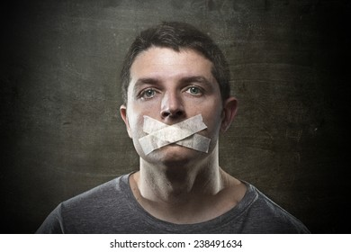 attractive young man with mouth sealed on duct tape to prevent him from speaking keeping him mute and censored in freedom of speech and expression concept isolated on dark grunge studio light style