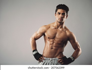 Attractive young man with muscular physique posing on grey background. Hispanic male fitness model standing with his hands on hips.