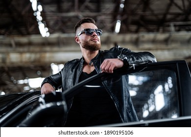 Attractive young man near car. Attractive elegant serious man near good car. Macho man in luxury auto. Selective focus.