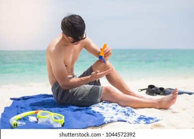 Attractive young man on the beach applying sunscreen to his body.