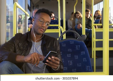 Attractive young man on the bus. He has earphones in which are attached to his smartphone, which he is holding in his hand and using.