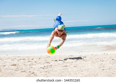 attractive young man playing volleyball on the beach summertime