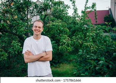 Attractive young man, portrait of a handsome guy, sincerely smiling on a background of greenery