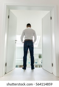 Attractive young man posing in white modern interior