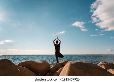Attractive young man practicing yoga meditation and breathwork outdoors by the sea