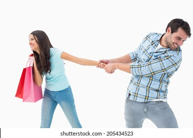 Attractive young man pulling his shopaholic girlfriend on white background