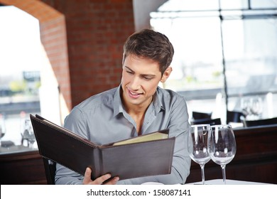 Attractive young man in a restaurant looking at the drinks menu